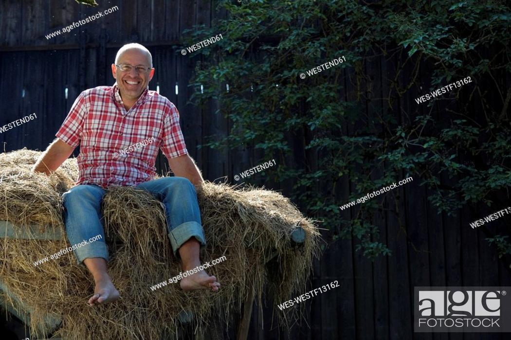 Stock Photo: Germany, Bavaria, Senior man sitting on haystack.