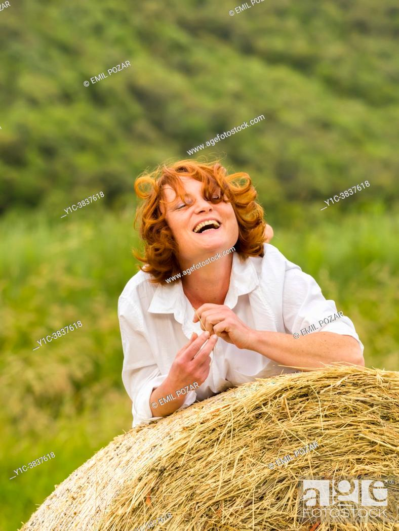 Imagen: Mature woman on countryside haystack is laughing squinting eyes.