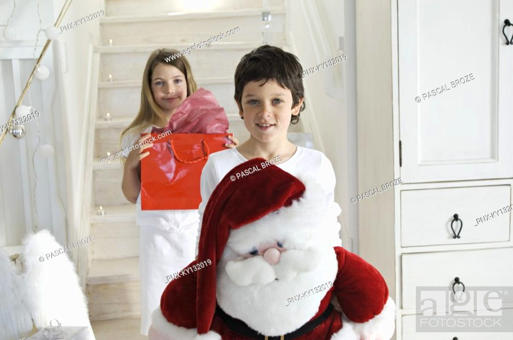 Stock Photo: Christmas day, little boy holding a cuddly toy Santa Claus, looking at the camera, sister with present in background, indoors.