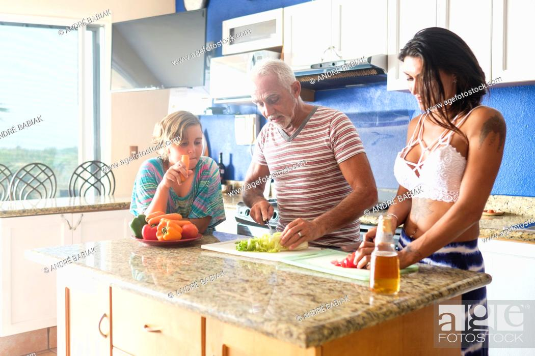 Stock Photo: Older man cutting vegetables in the kitchen with young attractive woman, child watchin.