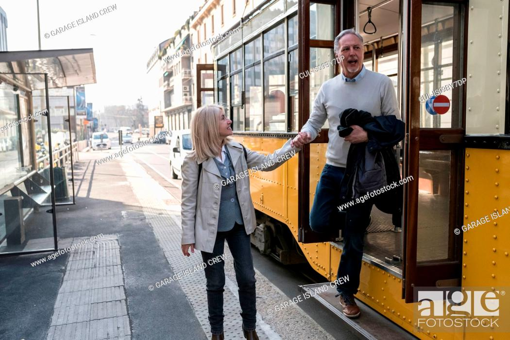 Stock Photo: Senior couple getting off tram in city.