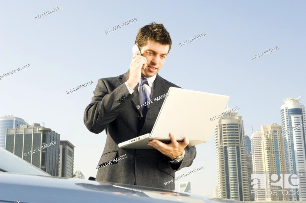 Stock Photo: A businessman talkingon a mobile phone holding a laptop.