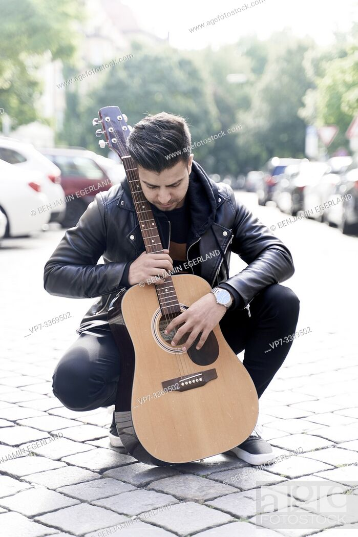 Stock Photo: Afghan man with acoustic guitar in hands at street in city Munich, Germany.
