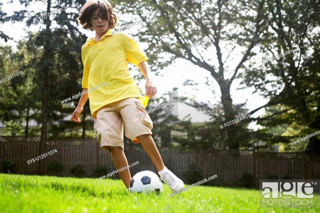 Stock Photo: Boy 12-13 playing with soccer ball.