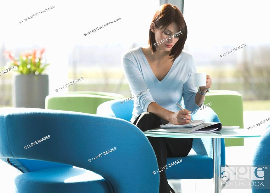 Stock Photo: A woman sitting at a table, having a drink and writing notes.