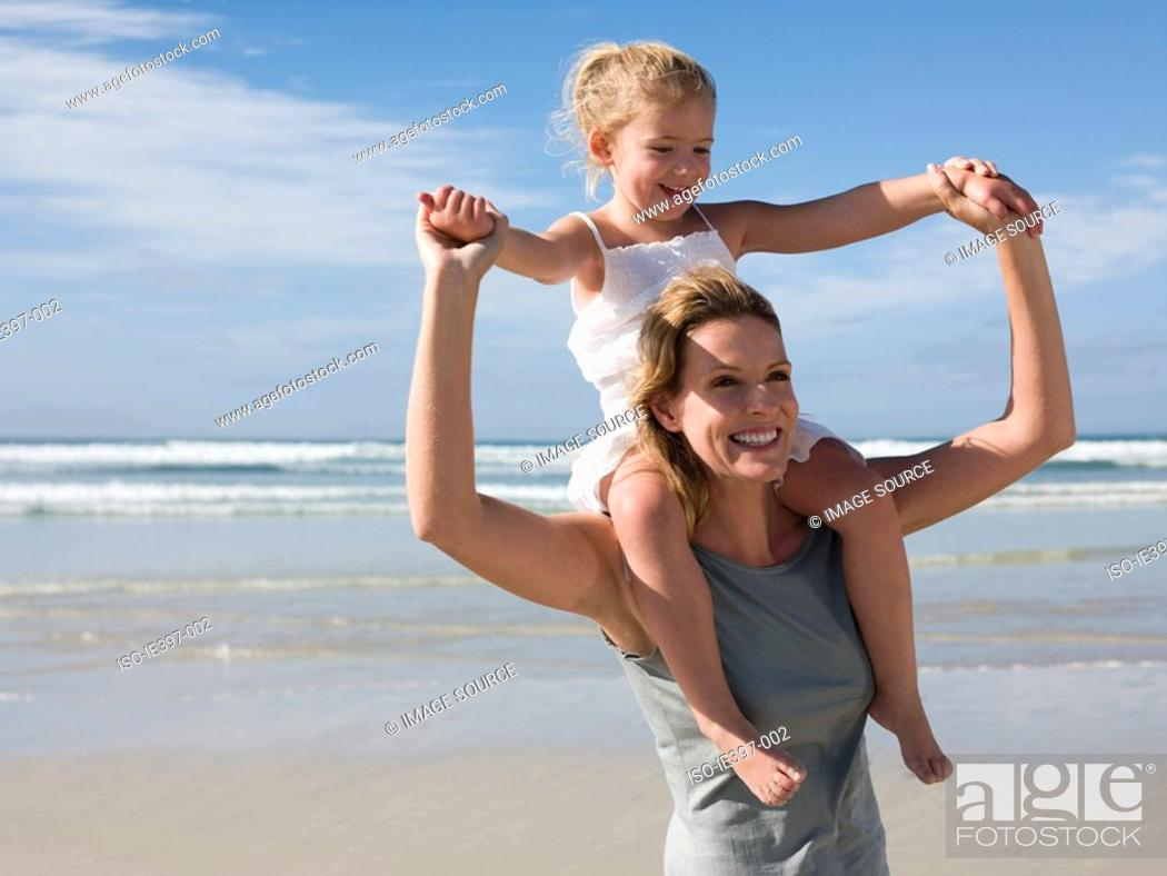 Stock Photo: Woman carrying daughter.
