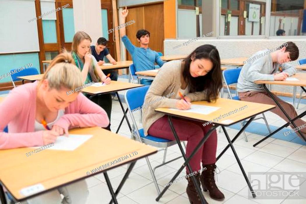 Stock Photo: Students sitting at the classroom while student is raising hand to ask question.