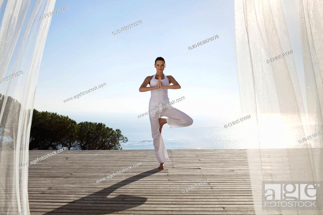 Stock Photo: Teenager practicing yoga on patio.