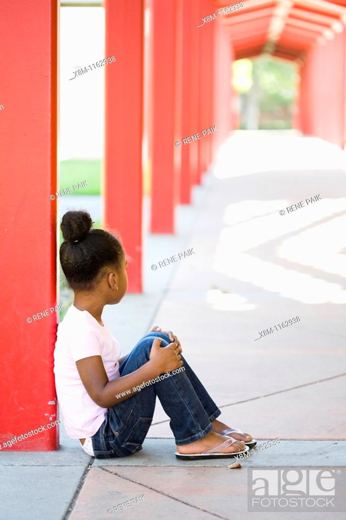 Stock Photo: A mixed race little black girl quitely sits in a school yard.