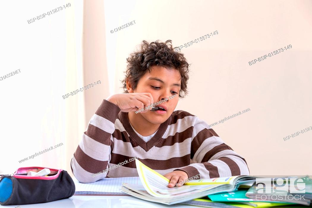 Stock Photo: Thoughtful teen boy doing homework at home alone.