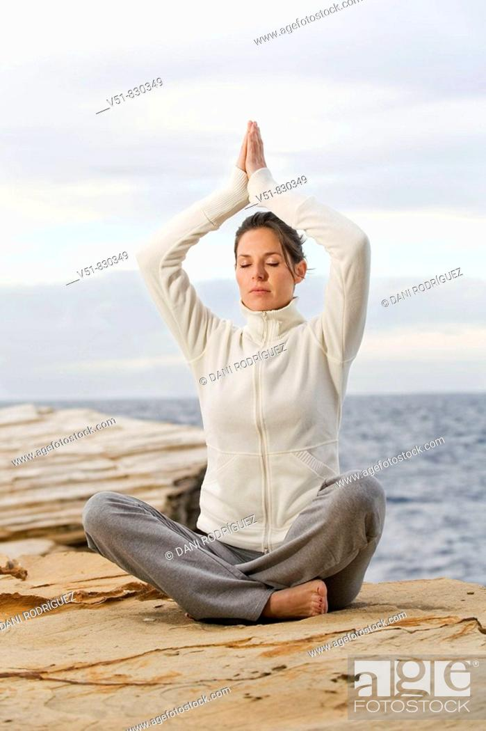 Stock Photo: Woman doing yoga in a cliff by the sea.