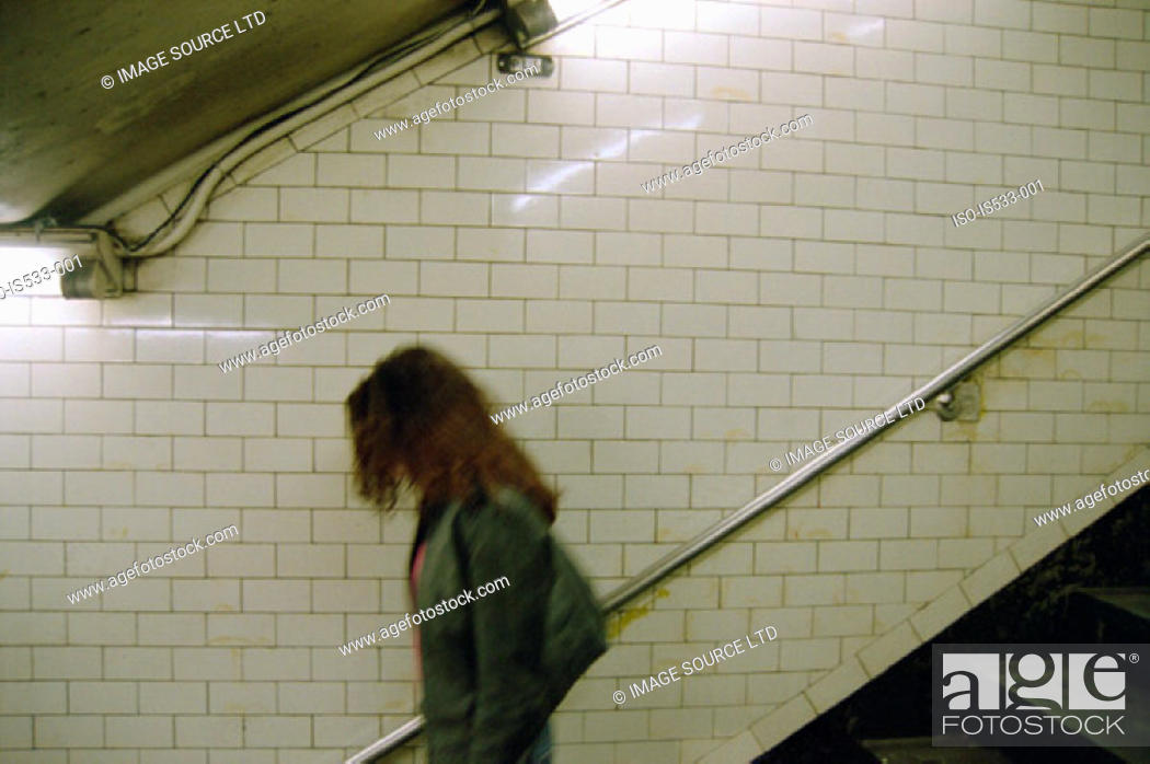 Stock Photo: Young woman walking down stairs.
