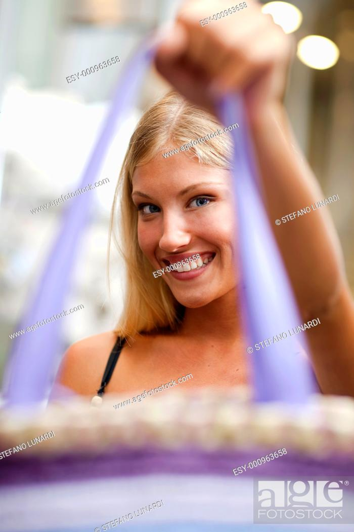 Stock Photo: Beautiful young woman showing a handbag.