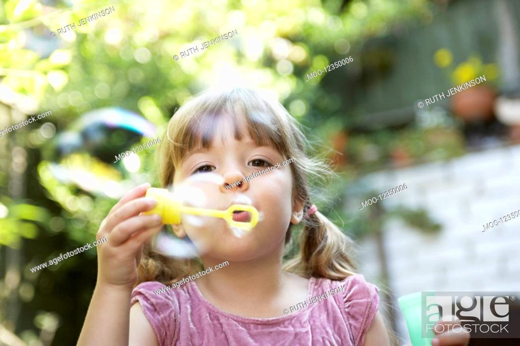 Stock Photo: Girl Blowing Soap Bubbles in backyard close up.