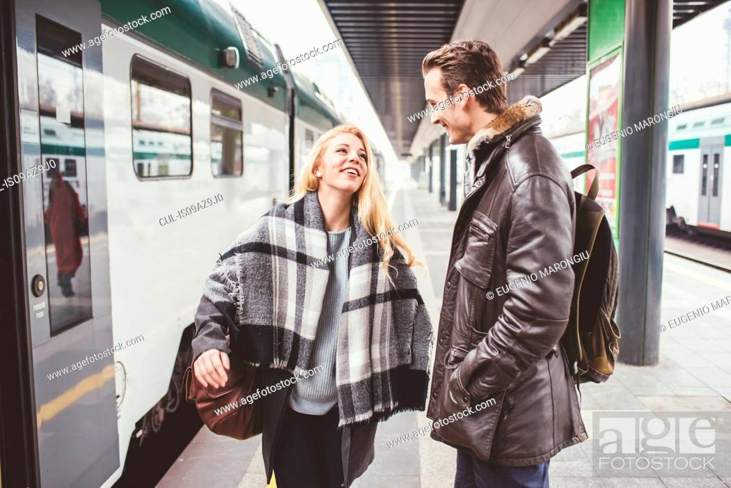 Stock Photo: Young couple departing on train station platform.