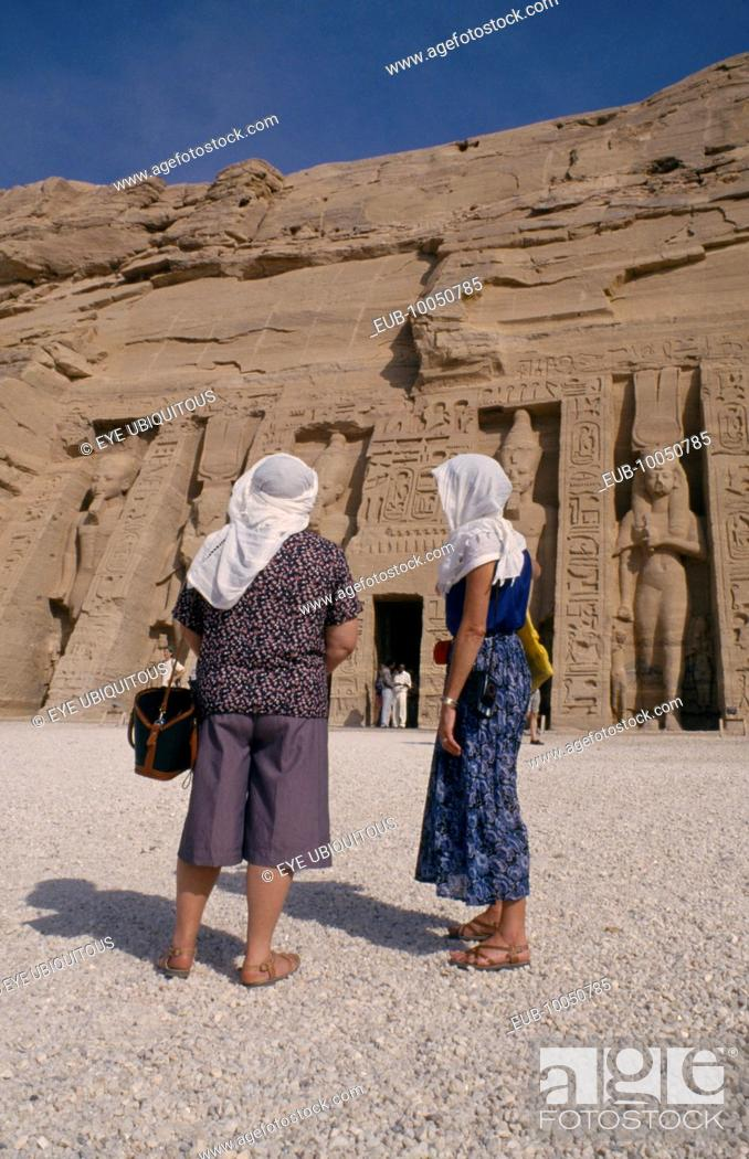 Stock Photo: Two female tourists wearing head scarves in front of staues of Ramesses II at the temple entrance.