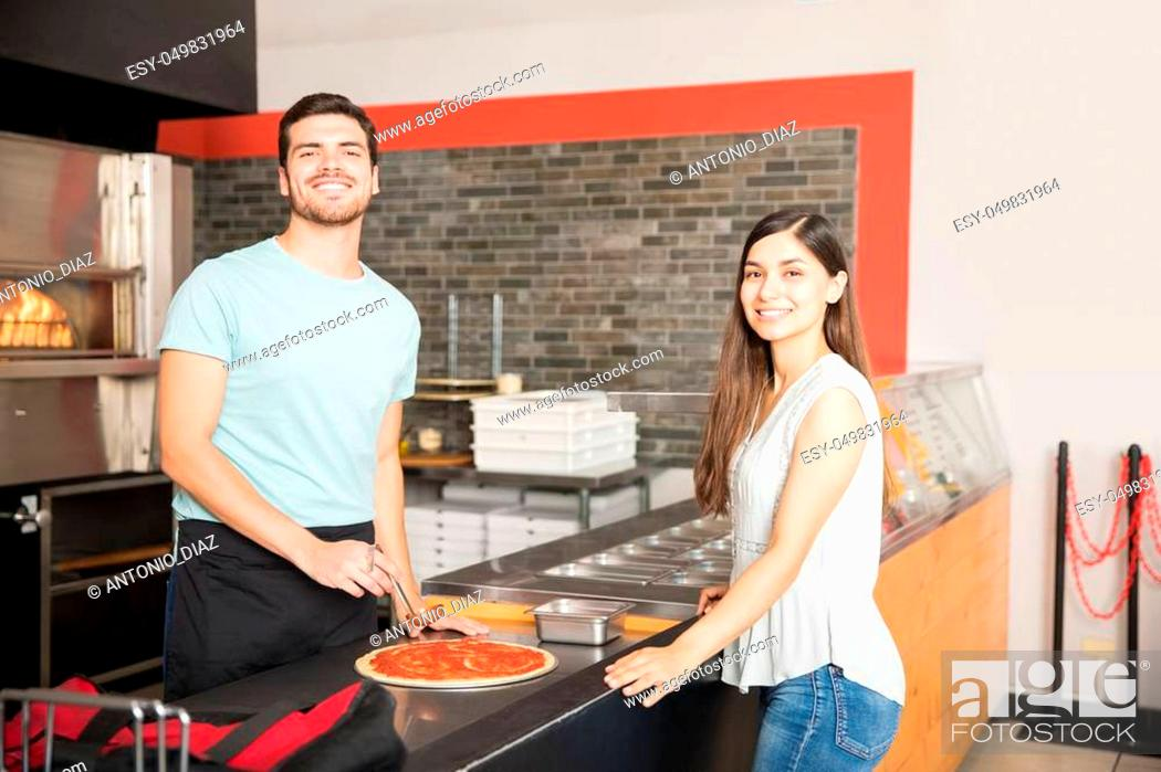 Stock Photo: Young smiling customer and chef standing at counter preparing pizza and looking at camera.