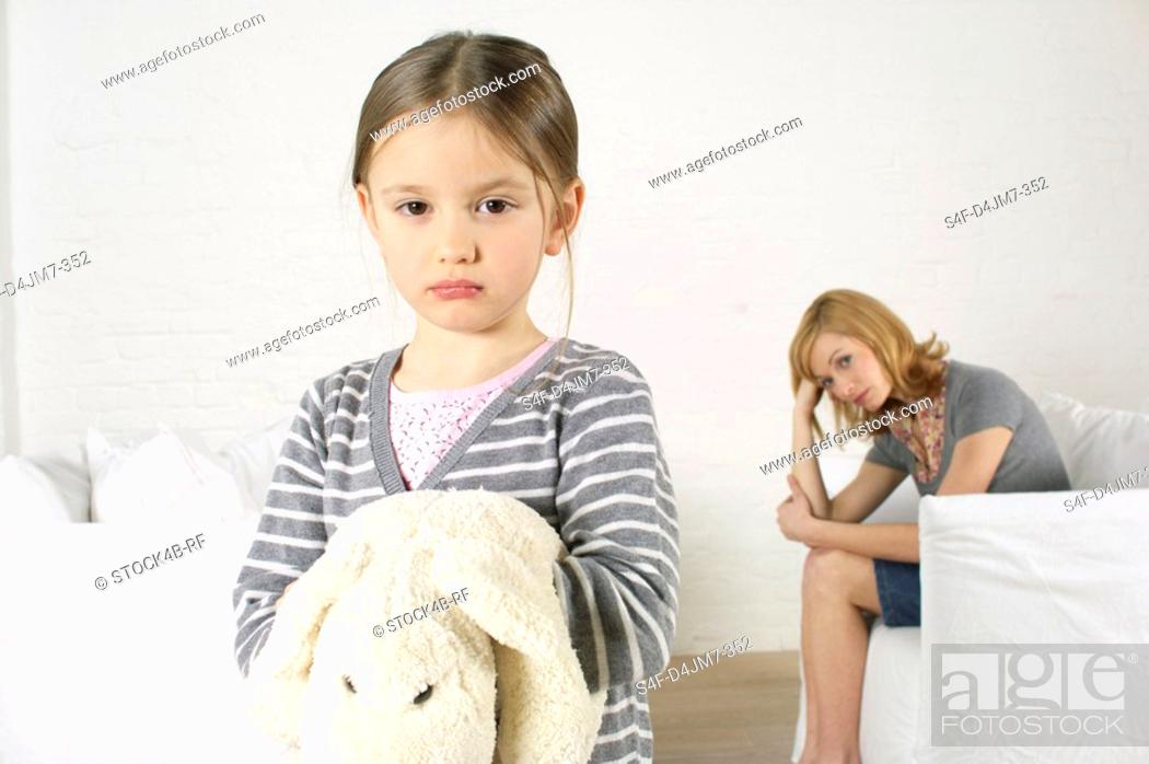 Stock Photo: Cheerless girl looking at camera, mother sitting in background.