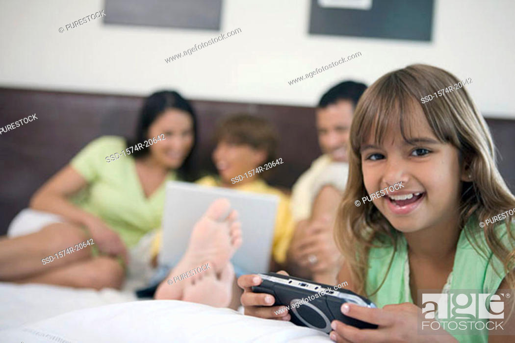 Stock Photo: Portrait of a girl holding a handheld video game with her parents and brother looking at a laptop in the background.