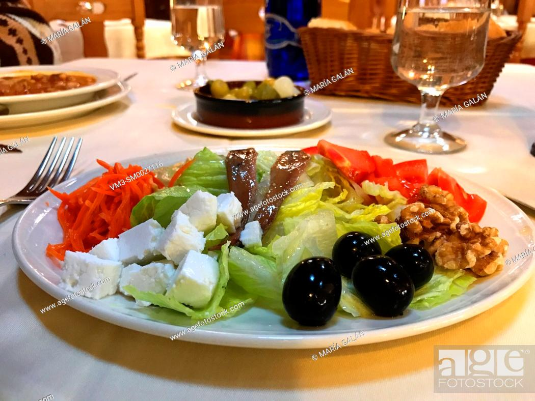 Stock Photo: Mixed salad made of lettuce, tomato, carrot, cottage cheese, black olives, anchovy filets, nuts and olive oil.