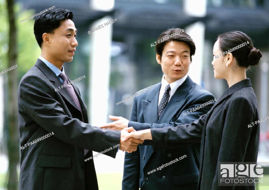 Stock Photo: Man and woman shaking hands, other man introducing them.