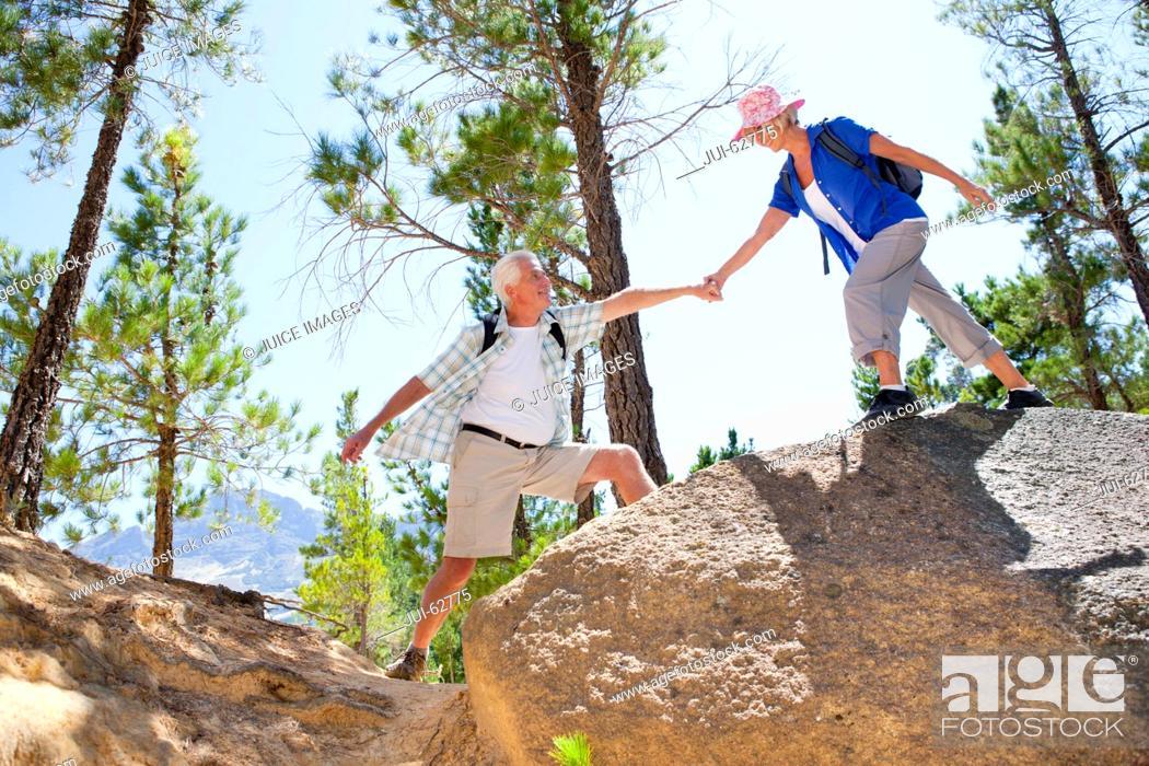 Stock Photo: Older couple hiking on rural hillside.