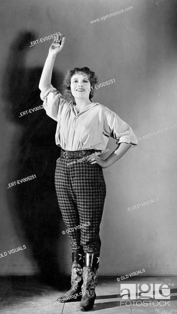 Stock Photo: Young woman standing with her hand raised and smiling All persons depicted are not longer living and no estate exists Supplier warranties that there will be no.