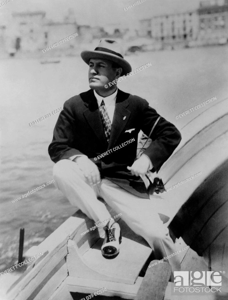 Stock Photo: Benito Mussolini seated on boat, facing left, wearing summer suit. Ca.1915-1925. - (BSLOC-2015-1-40).