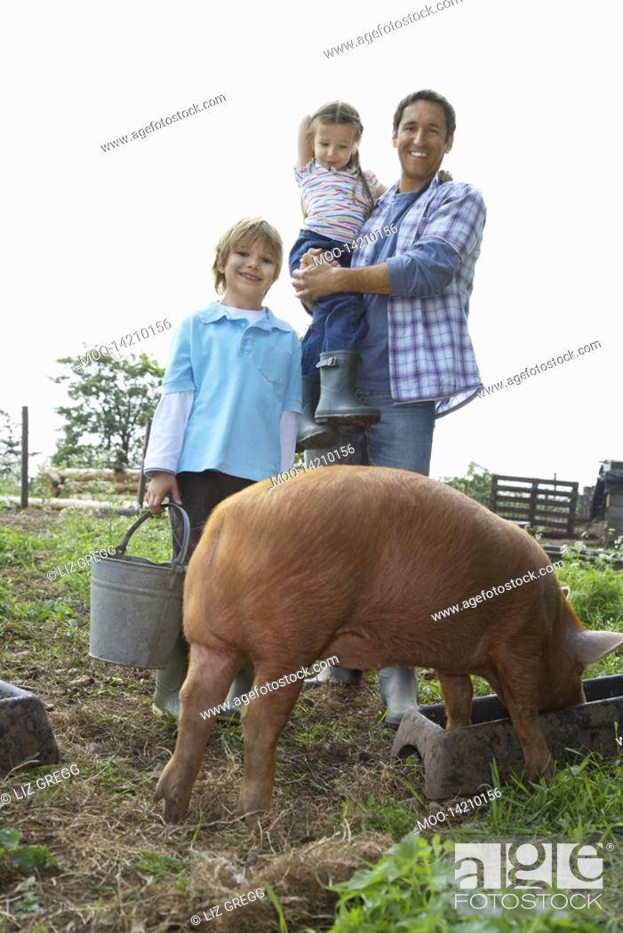 Stock Photo: Father and children 5-6 7-9 with pig in sty portrait.