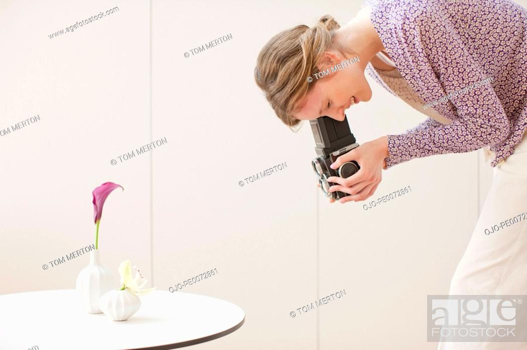 Stock Photo: Woman photographing flowers in vases with retro camera.