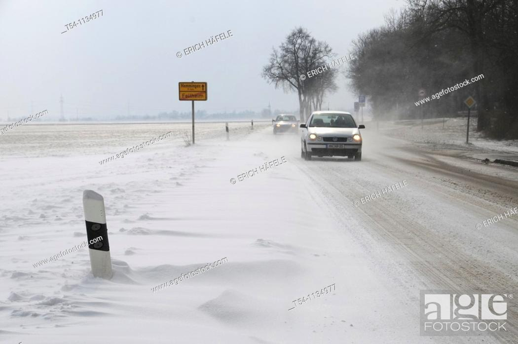 Stock Photo: Cars drive on a Street with snow banks.