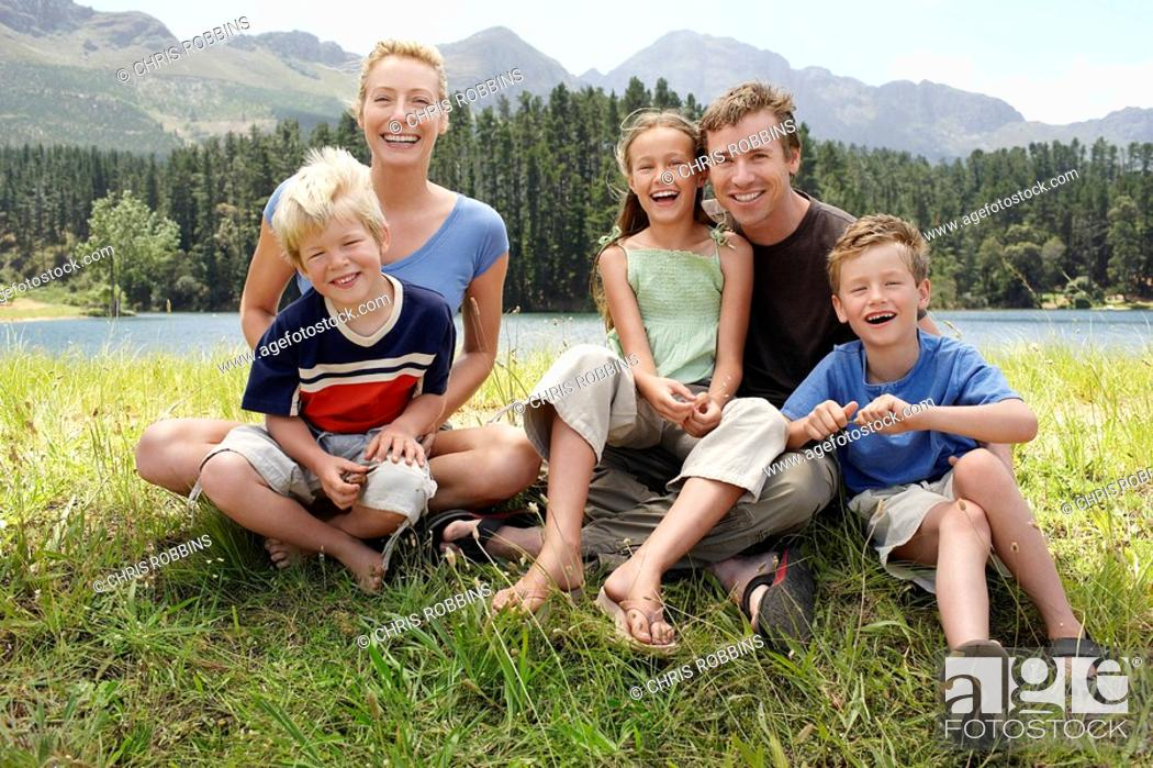 Stock Photo: Three children 7-9 sitting outdoors on grass with parents family portrait.