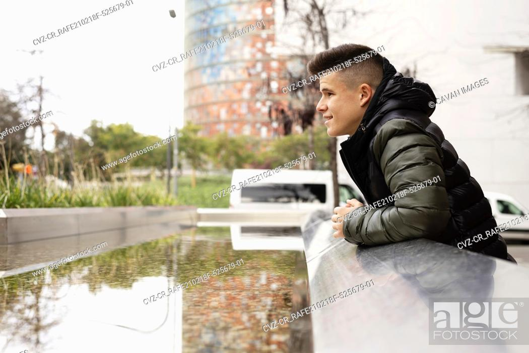 Stock Photo: Stylish happy guy leaning on wall looking away.