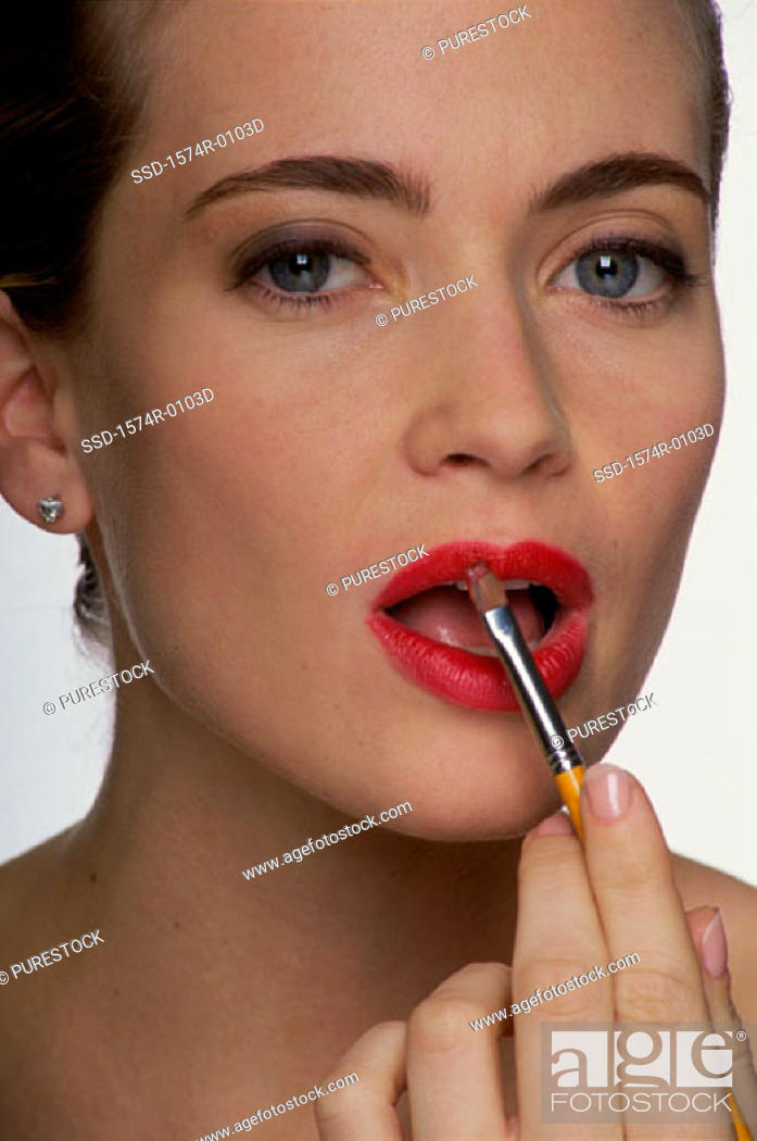 Stock Photo: Close-up of a young woman applying lipstick with a brush.