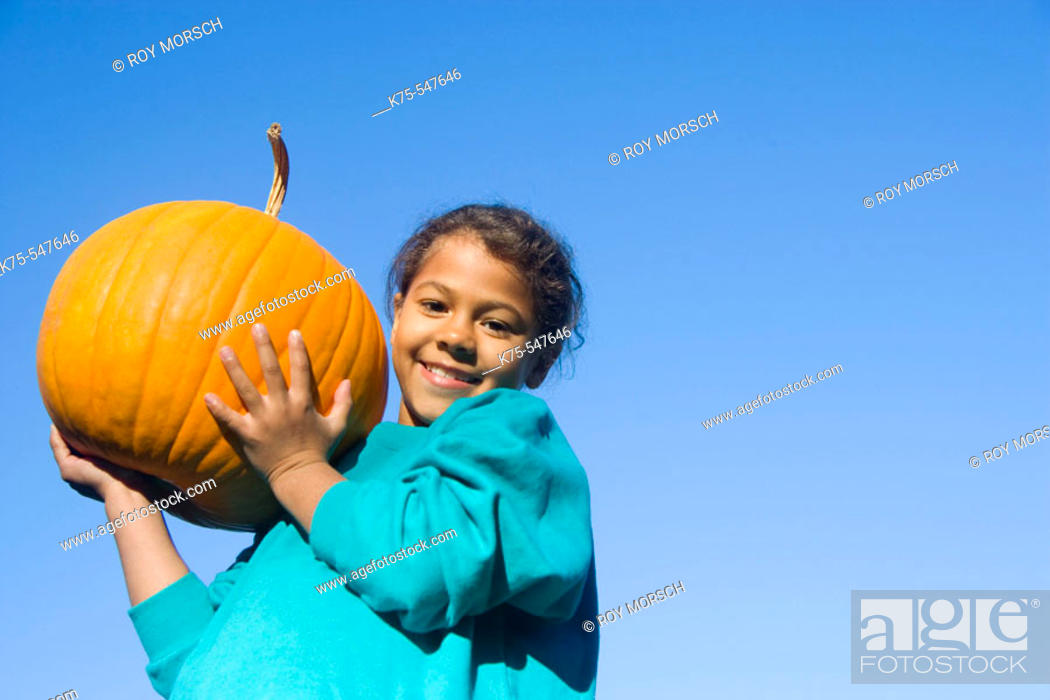 Stock Photo: Young girl holding big pumpkin.