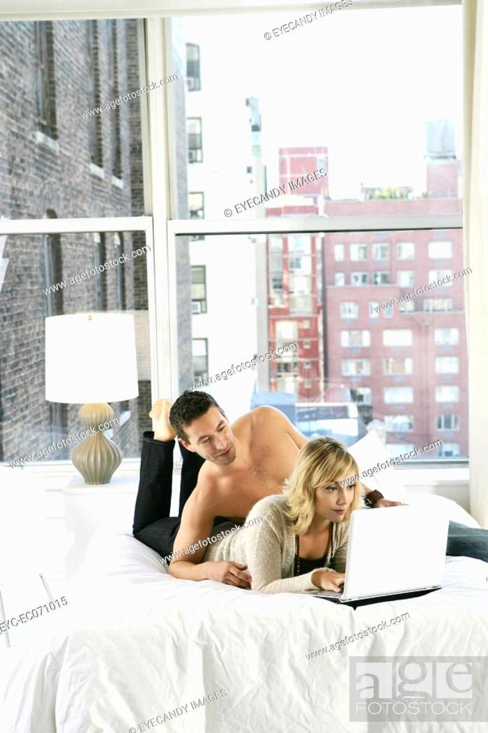 Stock Photo: Young couple using laptop in bed.