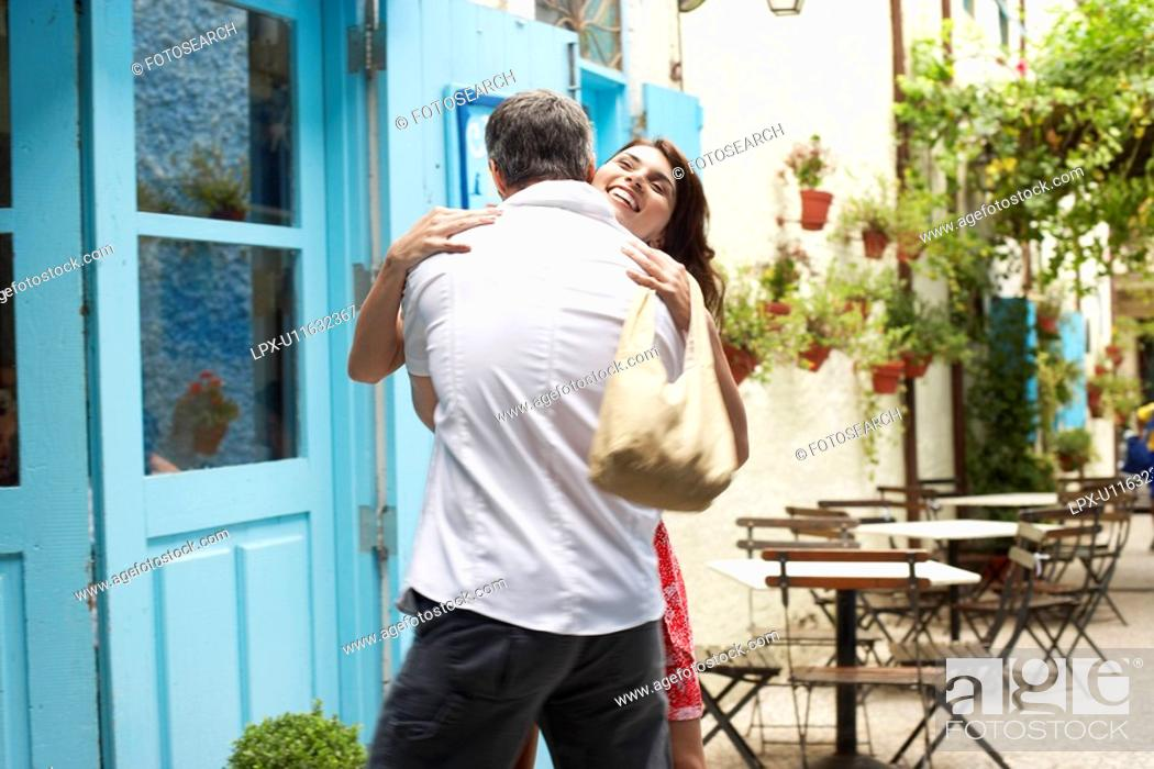 Stock Photo: Couple hugging outside café.