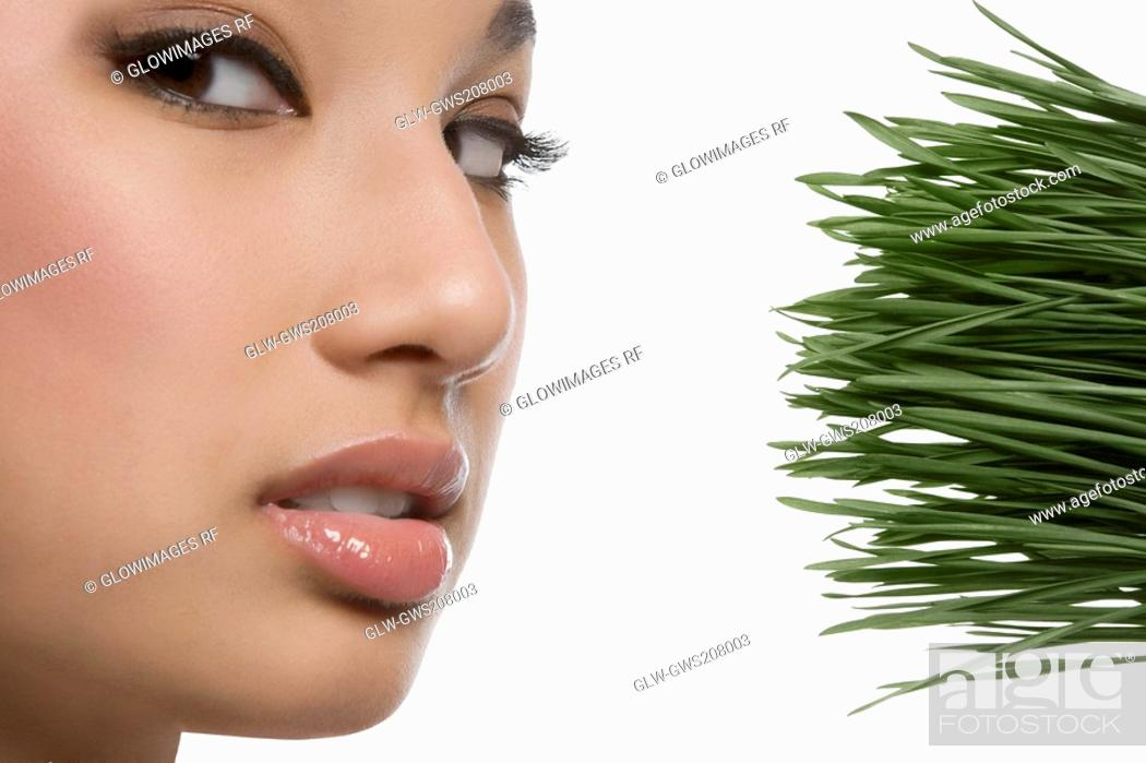 Stock Photo: Close-up of a young woman with wheatgrass.