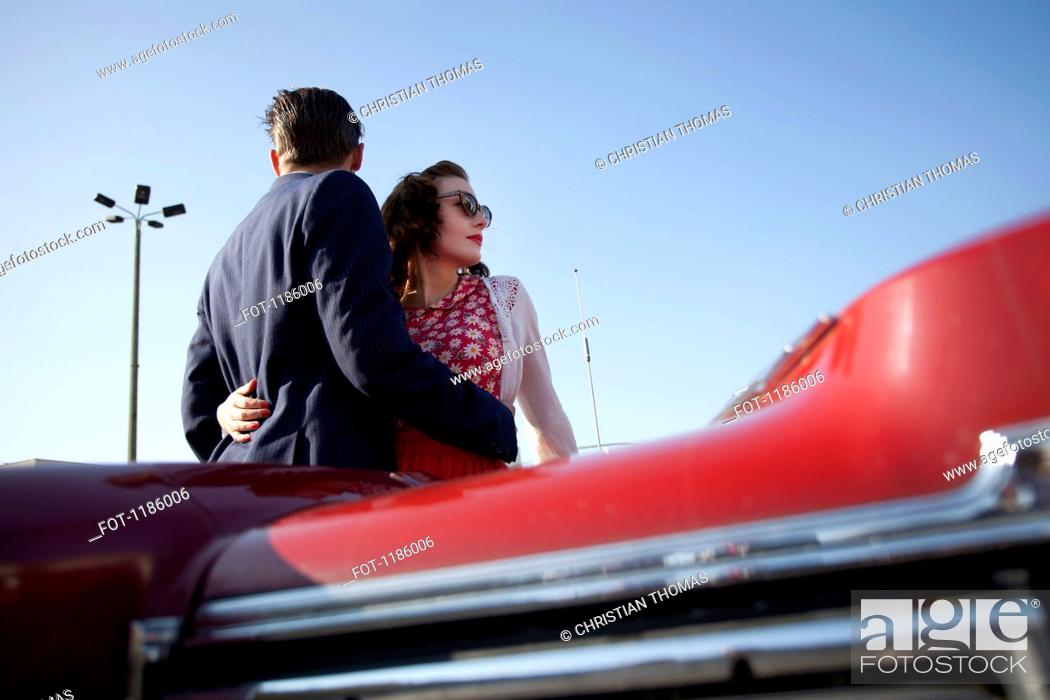 Stock Photo: A cool, rockabilly couple with arms around each other by a vintage car.