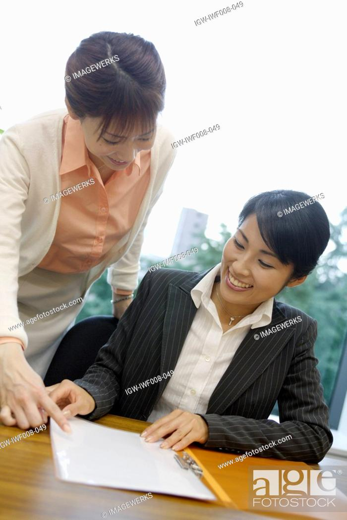Stock Photo: Two women exchange happiness as they look over the file.