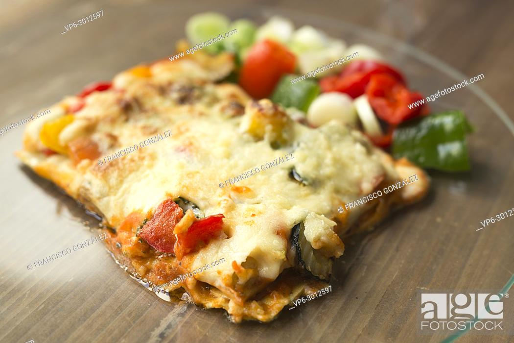 Photo de stock: Italian food known as lasagna on a glass plate and a wooden background.