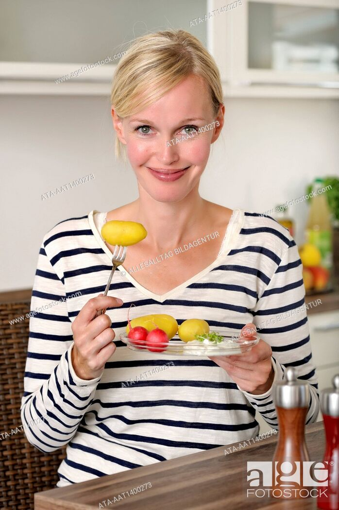 Stock Photo: Woman is eating potatoes with cottage cheese.