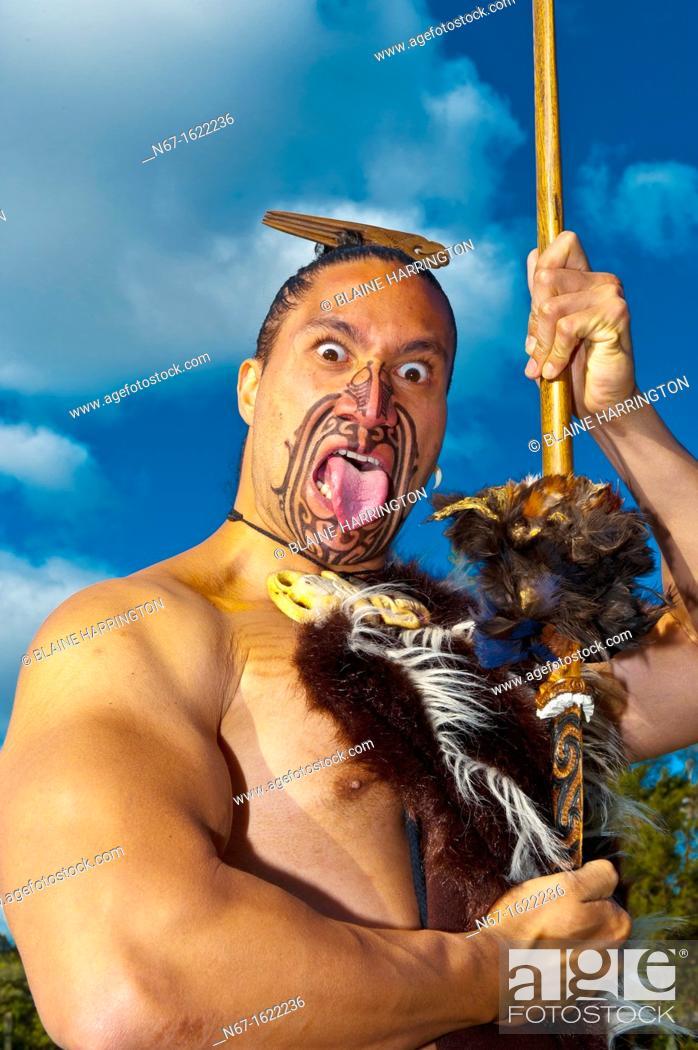 Stock Photo: A Maori warrior with a ta moko facial tattoo performs a war haka dance, Te Puia New Zealand Maori Arts & Crafts Institute, Rotorua, New Zealand.