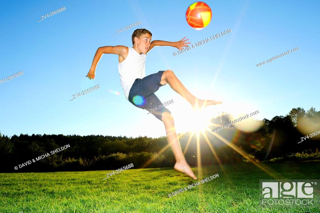 Stock Photo: Young boy playing soccer on a meadow, Germany.