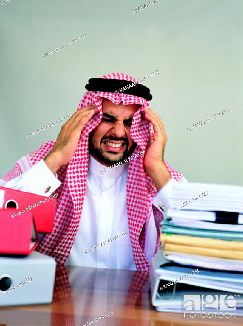 Stock Photo: Arab businessman stressed out at his desk.