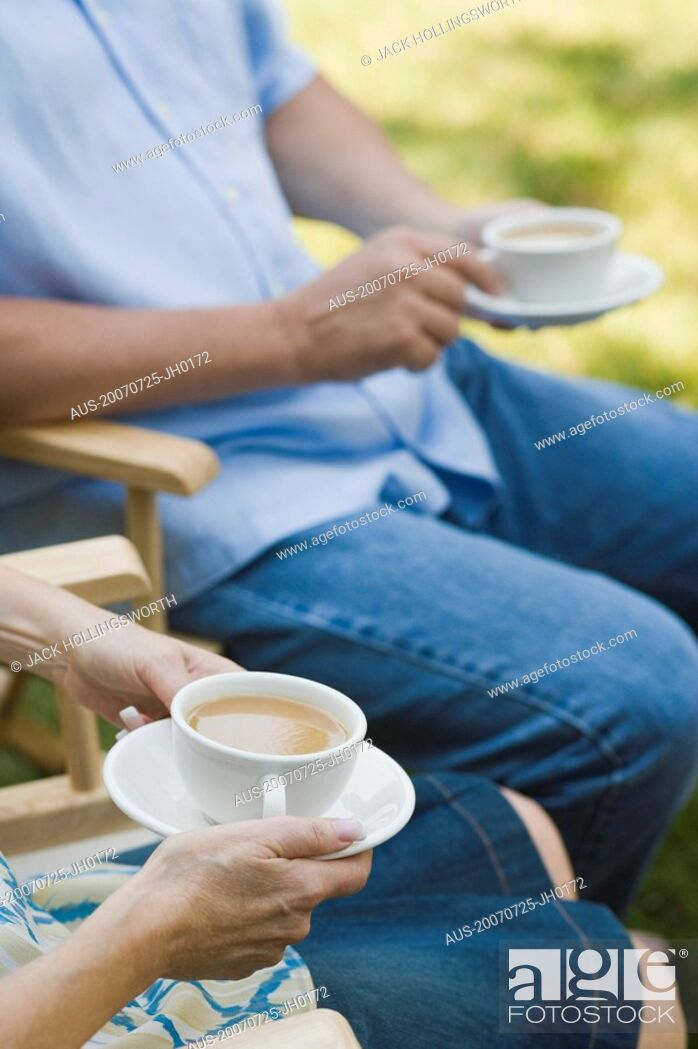 Stock Photo: Mid section view of a mature couple holding tea cups.