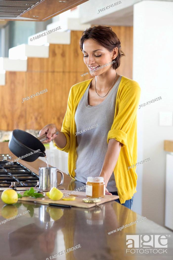 Stock Photo: Woman preparing herbal tea in the kitchen.