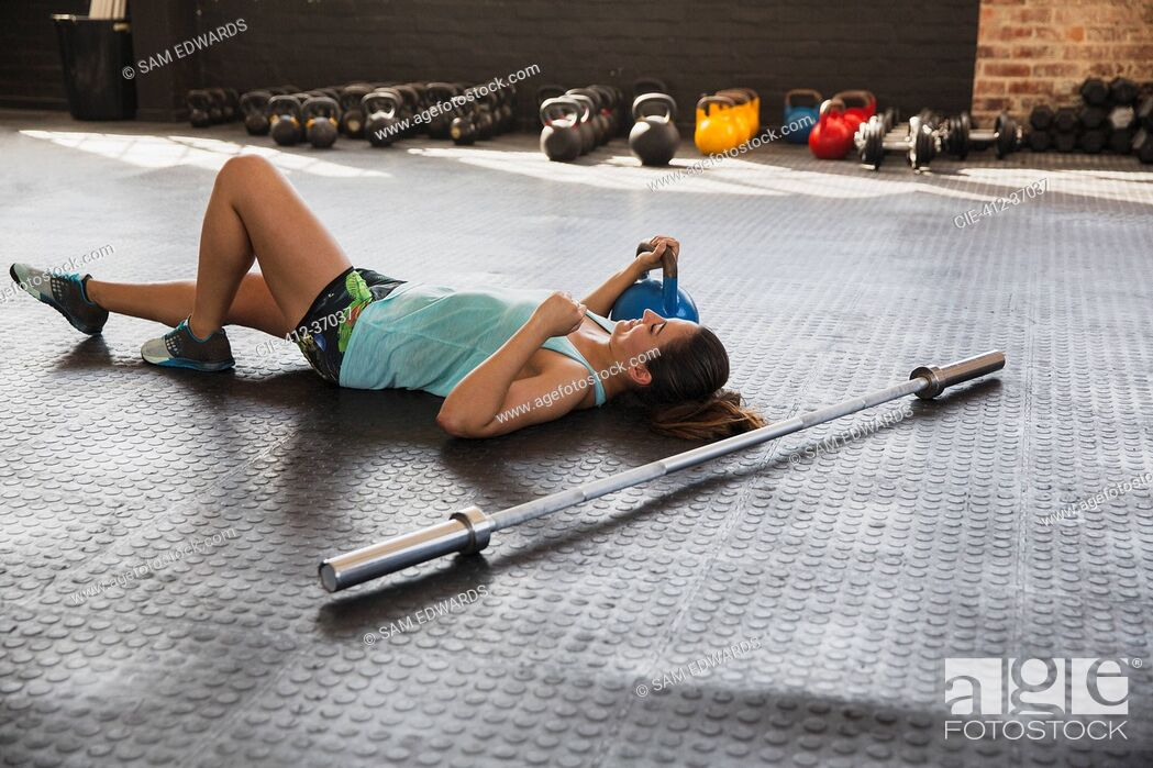 Stock Photo: Young woman resting, laying on gym floor next to barbell and kettle bell.
