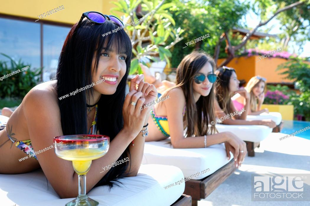 Stock Photo: Four attractive and pretty women in bikinis enjoying a day at a swimming pool with cocktails.