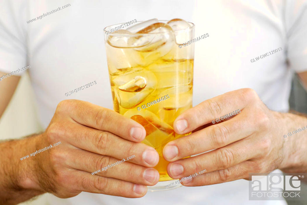 Stock Photo: Mid section view of a man holding a glass of whiskey.